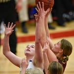 Cathedral's Julia Meyer (left) and Sauk Centre's Rebecca Weir reach for the rebound under Sauk Centre's basket during the first half Friday, March 11, in the 6-2A title game at Halenbeck Hall.