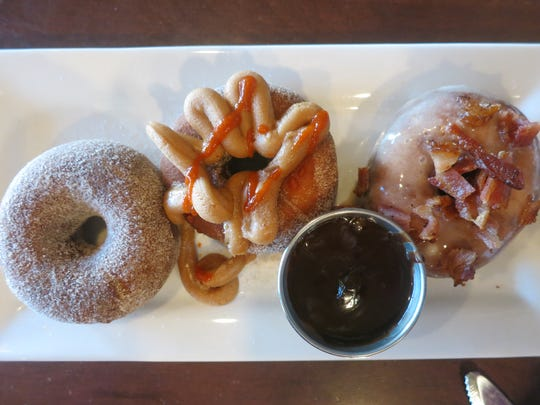 The doughnuts served at One-Eyed Betty's in Ferndale inspired plans for mini-doughnuts on the menu of the upcoming Daily Dinette, also in Ferndale. Shown are cinnamon-sugar, peanut butter-siracha, chocolate dipping sauce, and maple-bacon