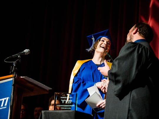 Debbie Miller receives the YTI Career Institute York Campus President's Award from pharmacy technician program coordinator Thad Graham during graduation at LCBC Manheim on Tuesday, Feb. 16, 2016.