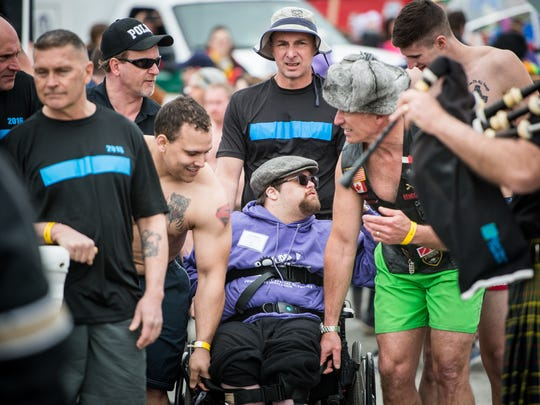 Special Olympics athlete and volunteer Noah Rinehart, who is paralyzed from the waist down, is escorted to the water by law enforcement officers and the Blue Line Plungers team during the   Polar Plunge on Saturday.