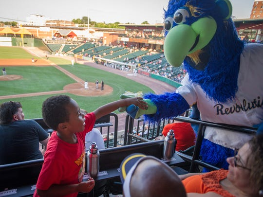 "Timothy Johnson, 6, makes contact with DownTown during Sensory Friendly Night at the York Revolution's game against the Somerset Patriots. Johnson's mother, Mia Boyd, said Timothy and her other son Micah, 5, would always cover their ears or get nervous when there was a lot of clapping at the game, anticipating a possible cannon blast. ""It seems more calm, people can just enjoy the game without the fear of that cannon going off,"" Boyd said of Sensory Night."