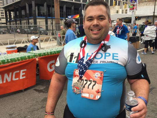Brian Welsbacher, 36, of Clawson enjoys finish-line water after he was one of more than 500 runners raising funds for the Hope Water Project, an annual marathon effort of Troy-based Kensington Church to drill water wells in Africa, Sunday, October 15, 2017.