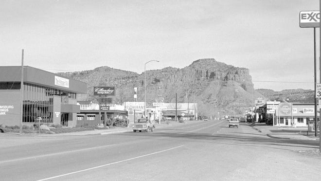 Downtown Kanab, seen looking east down Center Street from the west side of town in the then photograph, taken by Spectrum photographer Nancy Rhodes, shows the Williamsburg Savings Bank and the Exxon 1st Stop Gas Station in the foreground. The Williamsburg Bank is now a Mountain America Federal Credit Union branch and Exxon gas station is an empty lot. The Chef's Palace restaurant and the Treasure Trail Motel — whose signs can be seen standing just east of the Williamsburg Bank in the then image — have recently been demolished and replaced with a new drug store and the new Comfort Suites Hotel, both of which are rapidly nearing completion and can be seen in the now image taken by Spectrum photographer Jud Burkett.