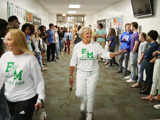 Fort Myers High School track and field coach Sheryl Jones, center, celebrates with the team on Thursday during a send-off march through Fort Myers High School. The Green Wave are headed to the state championships in Jacksonville.