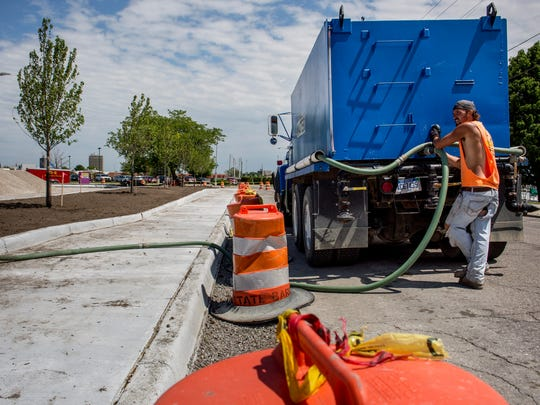 Contractor David Simpson control the flow of water from a truck while watering recently planted trees Thursday, June 23, 2016 at Quay and Fort streets in Port Huron. The parking lot is expected to be completed by June 30.