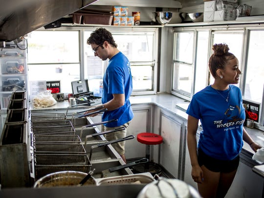 Adam Seely, 22, of Marysville, and Sophie Jackson, 18, of Port Huron prepare an order Monday, June 19, 2017 at The Wicked Fish at Vantage Point in Port Huron.