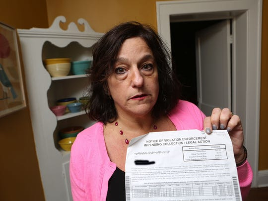 Janet Berg of Ossining has been fighting over EZPass and cashless tolling for a dozen years, getting the runaround from EZPass NJ, EZPass NY, The Port Authority, the DMV and collection agencies. It got so bad, she faced nearly $5,000 in fines and she was days from having her license suspended. She took $5K from her IRA to pay her debt in tolls and fines. Berg with one of her bills at home in Ossining Feb. 6, 2018.