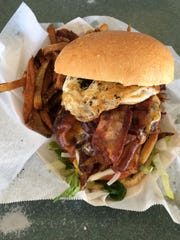 The hangover burger from The Doghouse comes with cheddar cheese, fries, bacon and a fried egg.