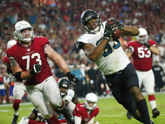 Former Cardinals defensive end Calais Campbell picks up a fumble before scoring during the fourth quarter on Sunday.