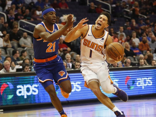 Phoenix Suns guard Devin Booker (1) is fouled by New York Knicks guard Damyean Dotson (21) during the first quarter in Phoenix on Wednesday.