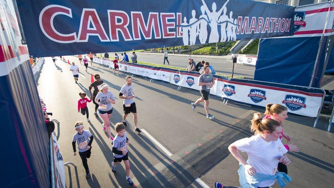 Runners competing in the 5k race cross the finish line. A few thousand runners competed in the 6th Annual Carmel Marathon Saturday, April 16, 2016.