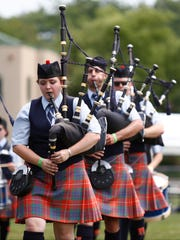 Members of the Empire Pipe Band march during the ceo˜l