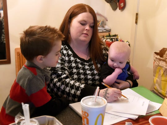 Andrea Ross of Evansville works on a skills test with help from her 7 month-old Easton McCraw and 5 year-old Zaydon Ross at a friends house after attending a high school equivalency class at PotterÕs Wheel in Evansville Wednesday.  Ross is taking classes to help her acquire her diploma.