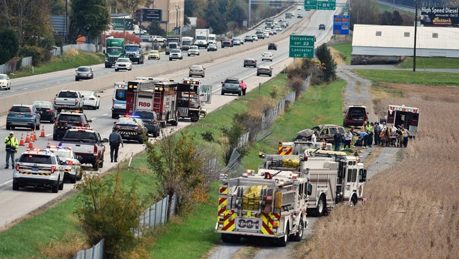 Emergency responders work on the scene of a one-vehicle crash Friday off Interstate 83 southbound, north of the George Street exit.