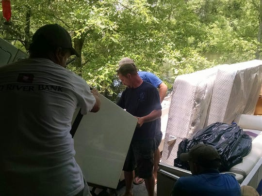Friends help the Bowers move everything out of their home on party barges.