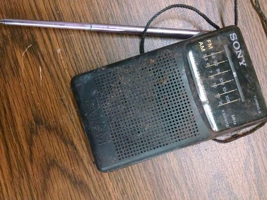 This small, blue, old-fashioned transistor radio was found with the body.