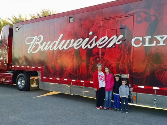 Chloe, Dakota and Logan Mandres stand in front of the Budweiser Clydesdales truck with their great-grandmother Alice Louchart