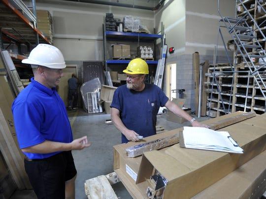 Jason Bake, left, talks with warehousemen Randy Little at Lumber Yard Supply.