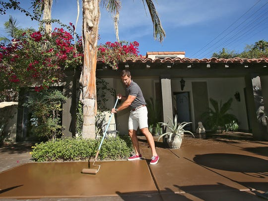 Vacation rental owner Rudi Polak refreshes the paint at the entrance to his property on Camino Carmelita in south Palm Springs.