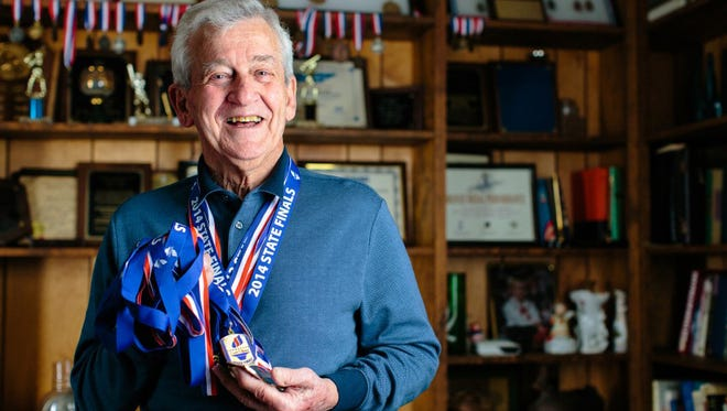 Sam Tomlin proudly displays his swimming medals.