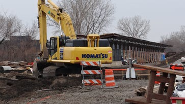 An excavator works on the site of the new Amtrak station. The old boarding platform is visible in the background.