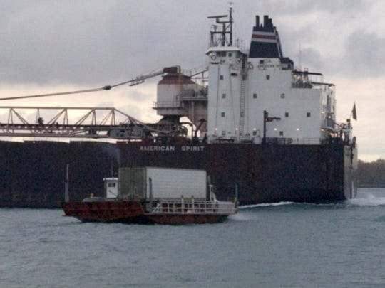 The Blue Water Ferry hauling a tractor-trailer is dwarfed by the freighter American Spirit in the St. Clair River near Marine City.