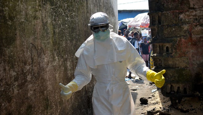 A Red cross worker wearing a protective suit gets ready for burial of Ebola victims in Monrovia on Jan. 5, 2015.