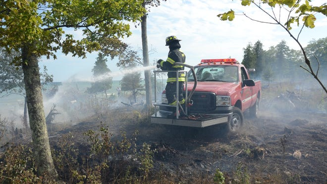 Firefighters from Washington Island and northern Door worked throughout the day and into the night Tuesday to extinguish a brush fire and cool hot spots.