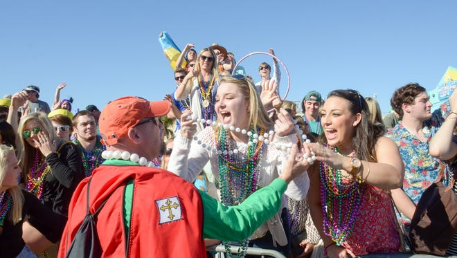A member of the Krewe of Andres de Pez passes out beads to the crowd during the 2016 Krewe of Wrecks Mardi Gras Parade on Pensacola Beach. The parade returns Sunday