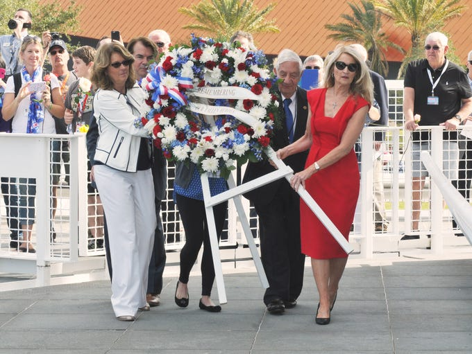 Family members of fallen astronauts place the wreath