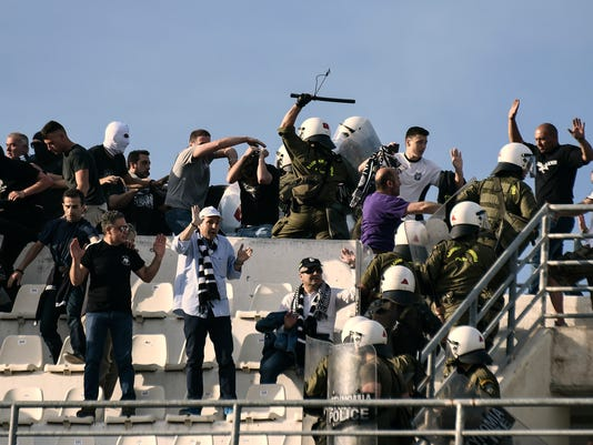 Policemen clash with soccer fans at a tribune of Panthessaliko stadium, ahead of the Greek Cup soccer final between AEK Athens' and PAOK in Volos, central Greece, on Saturday, May 6, 2017. (AP Photo/Giannis Papanikos)