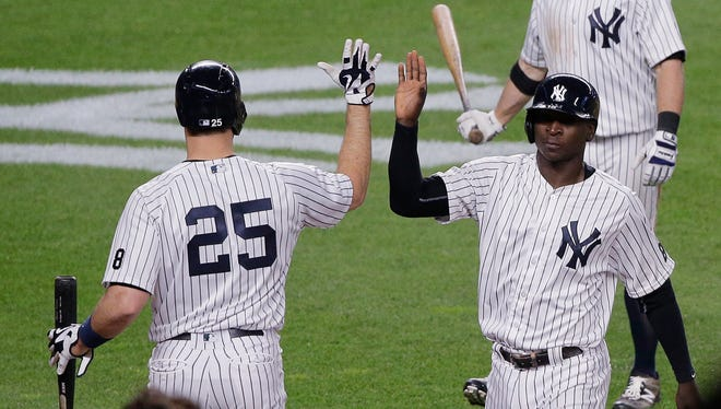 New York Yankees' Didi Gregorius, right, is greeted by Mark Teixeira (25) after scoring on an infield hit by Jacoby Ellsbury against the Toronto Blue Jays during the seventh inning of a baseball game, Tuesday, May 24, 2016, in New York.