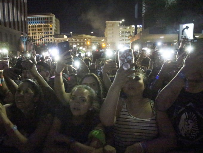 The crowd holds up lights on their mobile phones during