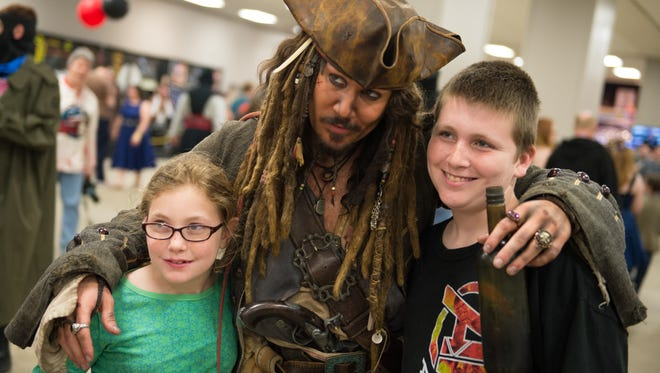 An actor dressed as Jack Sparrow poses with fans.