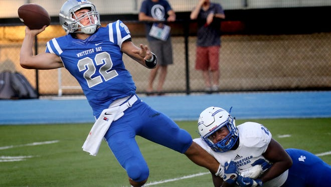 Whitefish Bay's Cade Garcia completes a pass while under pressure earlier this season. He passed for 245 yards and two TDs in rallying the Blue Dukes past Germantown, 32-25, on Sept. 23.