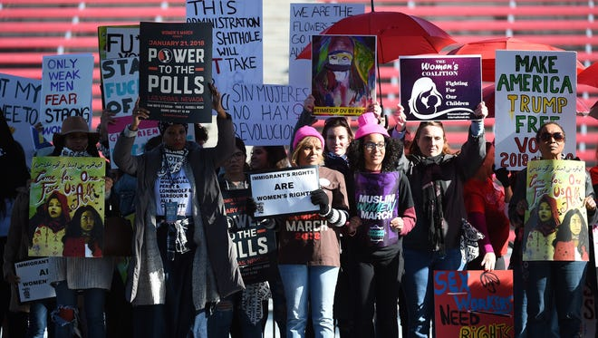 """Attendees hold signs onstage during the Women's March """"Power to the Polls"""" voter registration tour launch at Sam Boyd Stadium on January 21, 2018 in Las Vegas, Nevada. Demonstrators across the nation gathered over the weekend, one year after the historic Women's March on Washington, D.C., to protest President Donald Trump's administration and to raise awareness for women's issues."""