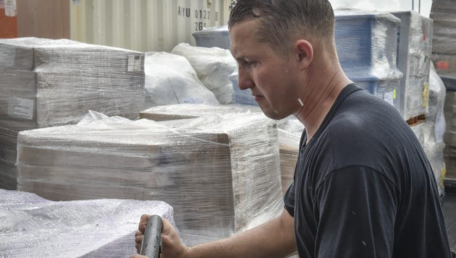 In this file photo, Shane Slater, boatswain's mate aboard the USS Ashland, arranges pallets of emergency water, food, and supplies on the ship's deck at on Naval Base Guam.