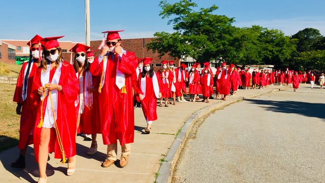 Wearing masks and sunglasses with their cap and gowns, BHS seniors march to a recorded orchestral version of Pomp and Circumstance and into Shields Stadium Saturday.