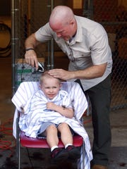 Randolph Detective Neil Caufield shaves the head of his son, Eamon, 3, as police officers and family members shaved their heads in support of cancer-stricken brother officer Reggie Crowley who lost his hair after chemotherapy.  July 16, 2018. Randolph, New Jersey