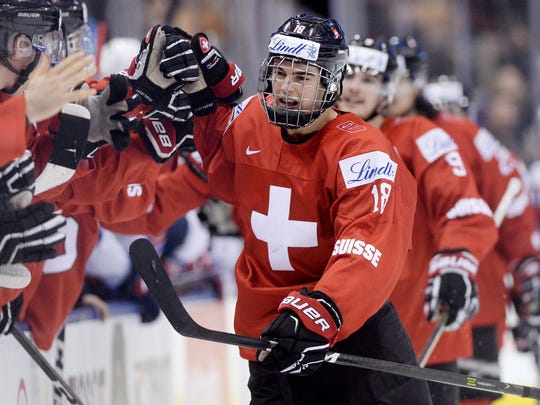 Switzerland forward Nico Hischier (18) celebrates with teammates at the bench after scoring against the United States during the third period of a quarterfinal hockey game at the world junior championship in Toronto, Monday, Jan. 2, 2017.