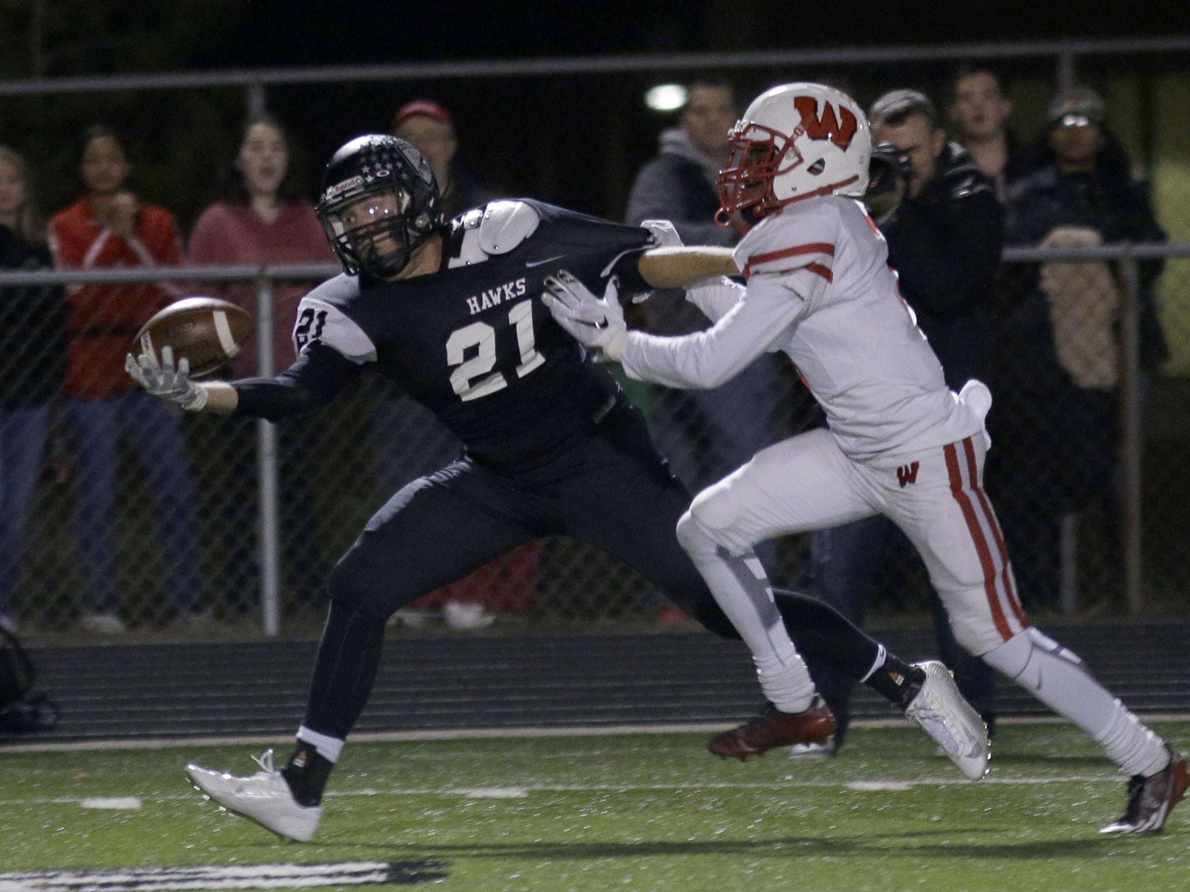 Lakota East's Austin Hatfield tries to catch the ball over Lakota West defender Jalen Hall during their game Friday. Lakota West won the game 35-0 and is headed to the playoffs.