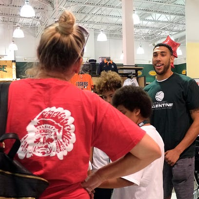 Former MSU basketball star and now NBA player Denzel Valentine, helps a youngster pick out some shoes at Dick's Sporting Goods in the Eastwood Towne Center Monday, July 25, 2016. Ten attendees of his basketball camp were chosen to go on a shopping spree with him.