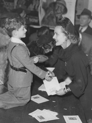 A 5-year-old boy received Carole Lombard's thanks as he purchased a $25 bond at an Indianapolis stop during her bond drive on Jan. 15, 1942.