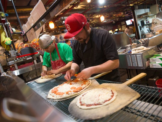 Zack Padilla, left, works on a calzone and Jeremy Collins adds pepperoni to a pizza Friday at the Three Rivers Pizzeria in Farmington.