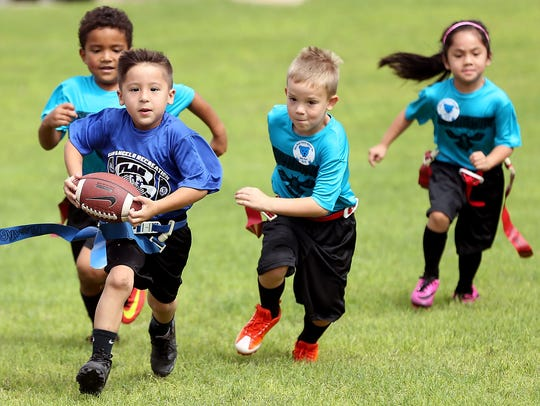 Children play in a flag football game at River Fest