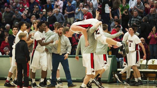 Rutland celebrates the win during the boys semifinal basketball game between the Burlington Seahorses and the Rutland Raiders at Patrick Gym on Tuesday night.