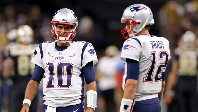 New England Patriots quarterback Jimmy Garoppolo (10) talks with Tom Brady (12) before their game against the New Orleans Saints at the Mercedes-Benz Superdome.