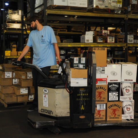 Marlon Milbourn picks liquor bottles for shipping at the Worcester County Department of Liquor Control in Snow Hill.