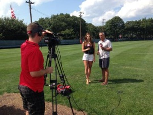 RVision reporter Taryn Hatcher interviews Rutgers senior director of digital media Tom Luicci after football practice earlier this week as Tim DeMartin rolls the camera for a piece on ScarletKnights.com. (Photo: Courtesy of Rutgers athletics communications )