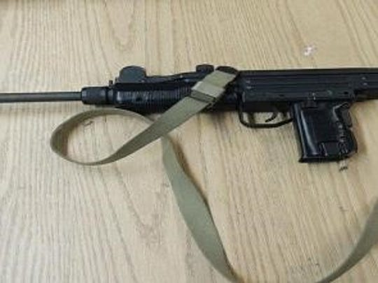 Elmira police display a stolen Uzi assault weapon seized after executing a search warrant Friday.